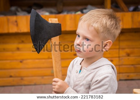 Little boy outdoors. The kid is holding a wooden ax. Boys playing in the street. Kids Games, carelessness, wooden toys - Concept of carefree childhood.
