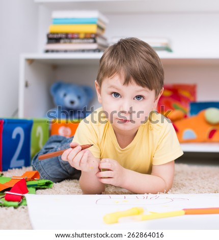 little boy painting with paintbrush and colorful paints - stock photo