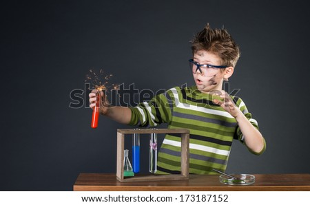 Little boy performing experiments. Crazy scientist. - stock photo