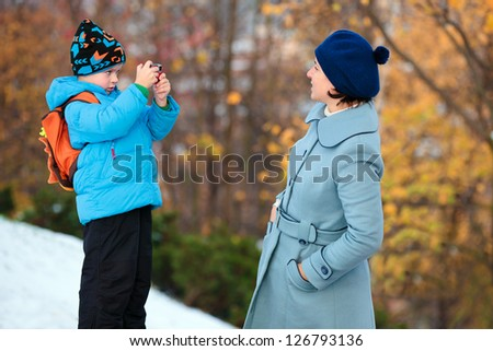 Little boy photographing his mother at autumn park