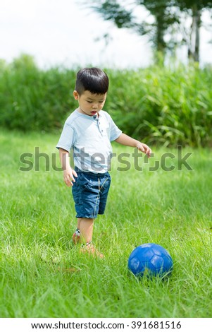 Little boy play football at outdoor - stock photo