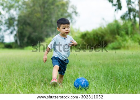 Little boy play soccer at outdoor - stock photo