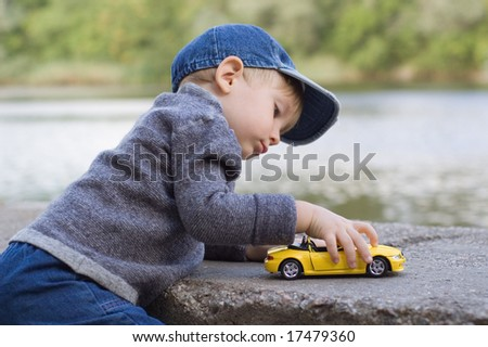 little boy play with a car outdoor - stock photo