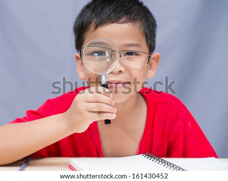 little boy play with book looking through magnifying glass
