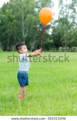 Little boy play with flying balloon at outdoor - stock photo