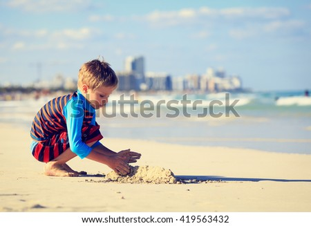 little boy play with sand on summer beach