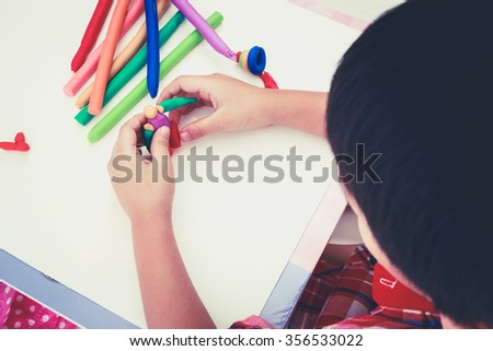 Little boy playing and creating toys from play dough, on white background. Child moulding robot modeling clay. Strengthen the imagination of child. Retro picture style. - stock photo