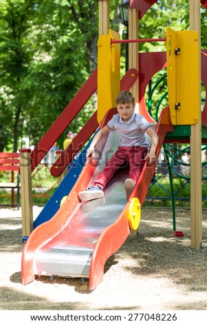 Little boy playing at playground on a sunny day - stock photo