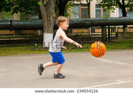 Little boy playing basketball running along the court in his sports wear bouncing the ball, side view outdoors - stock photo