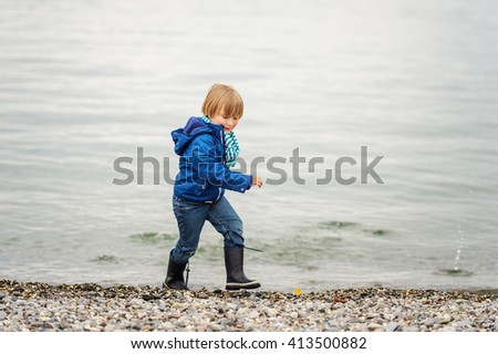 Little boy playing by the lake on a cloudy day - stock photo