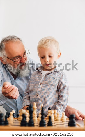 Little boy playing chess with his grandfather - stock photo