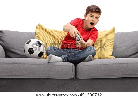 Little boy playing football video game seated on a sofa isolated on white background