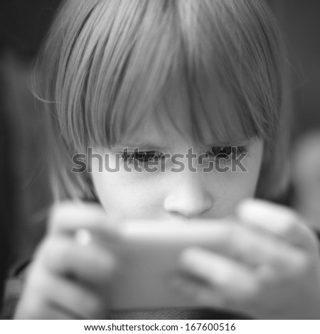 Little boy playing game on cell phone