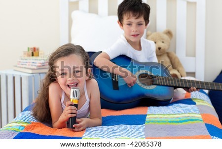 Little boy playing guitar and his sister singing in the bedroom - stock photo
