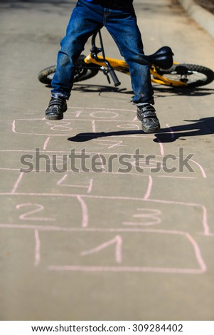 little boy playing hopscotch with bike, kids play outdoors - stock photo