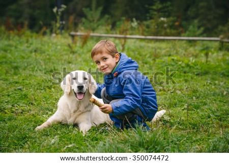 Little boy playing in forest lawn with a golden retriever. - stock photo