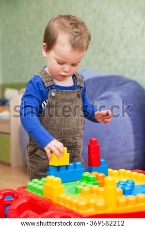 little boy playing in the children's designer home in the nursery - stock photo