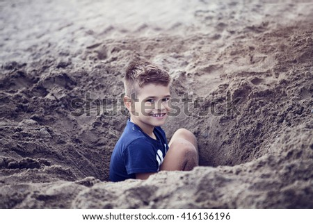 Little boy playing in the sand on the beach - stock photo