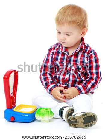 Little boy playing in the shop, he weighed on the scales of toy toy vegetables.White background, isolated photo. - stock photo