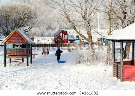 Little boy playing in the winter park - stock photo