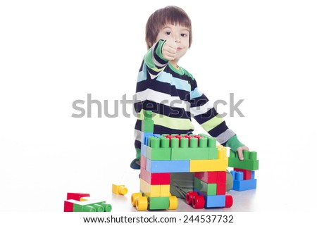 Little boy playing lego on the floor and showing hand ok sign - stock photo