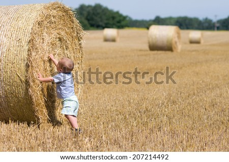 little boy playing on bales of straw on the field - stock photo