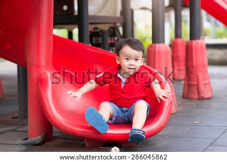 Little boy playing on children's slides. Outdoor portrait of a cute little asian boy at playground - stock photo