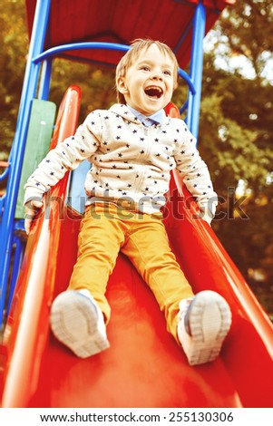 Little boy playing on children's slides. Warm filter and film effect - stock photo