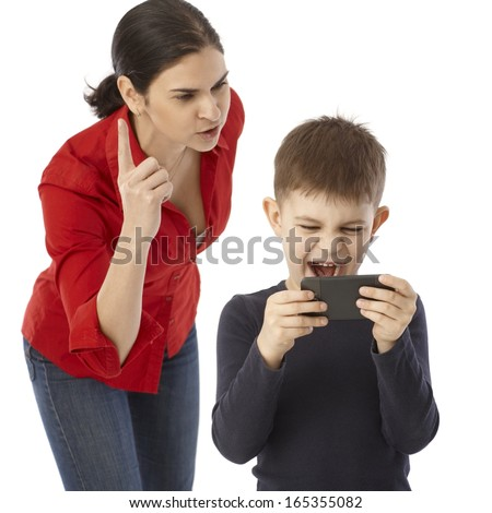 Little boy playing on mother's mobilephone, mother rebuking him. - stock photo