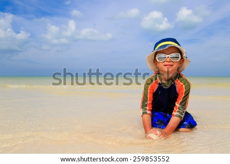 little boy playing on sand tropical beach - stock photo