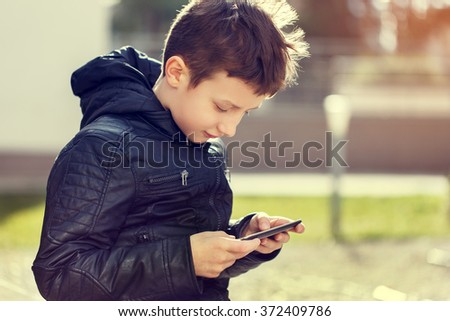Little boy playing on tablet outdoor in sunset - stock photo