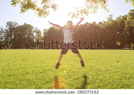 little boy playing on the grass in the summer park - stock photo