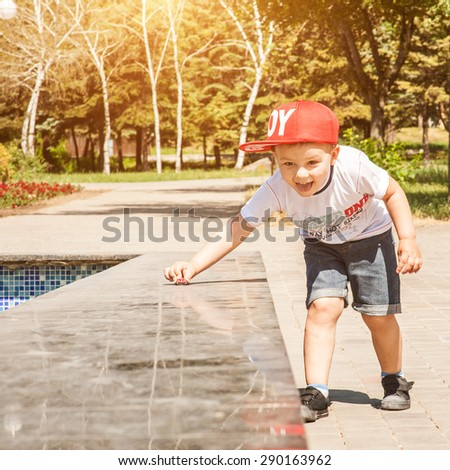 Little boy playing outdoors in the city in park, wheels toy car on a marble surface - stock photo