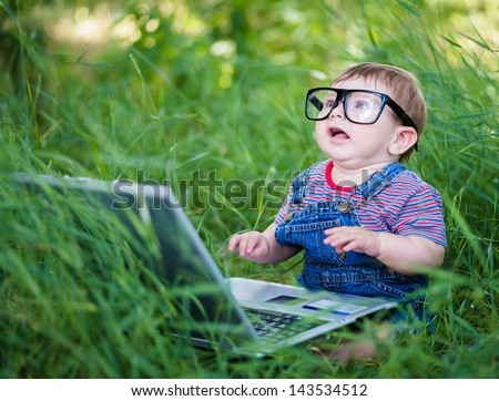 little boy playing outdoors with a laptop - stock photo