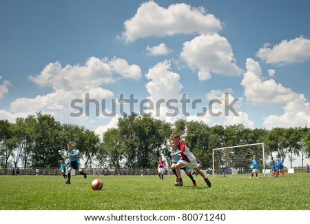 Little Boy playing soccer on the sports field - stock photo