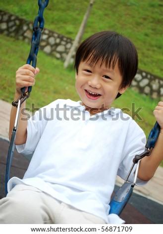 little boy playing swing - stock photo