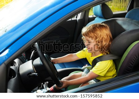Little boy playing to be a driver in parents car sitting on the first seat steering the wheel - stock photo