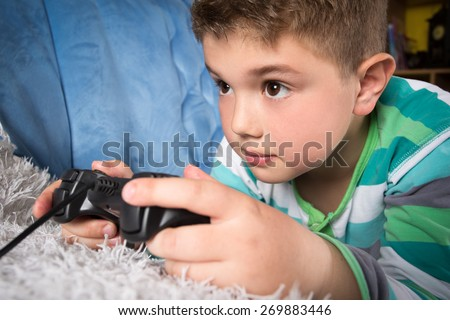 Little boy playing video games - stock photo