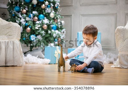Little boy playing with a toy dinosaur by Christmas tree - stock photo