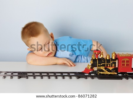 Little boy playing with a toy locomotive - stock photo