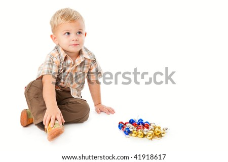 Little boy  playing with baubles. Isolated on white background