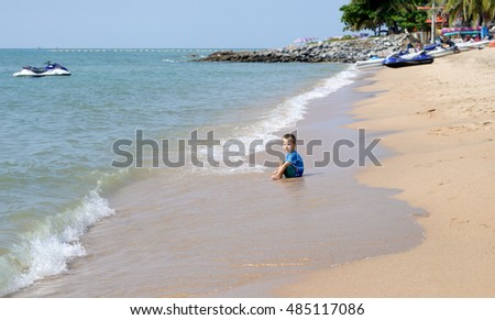 little boy playing with beach toys on tropical beach