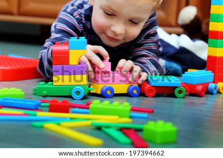 Little boy playing with blocks - stock photo