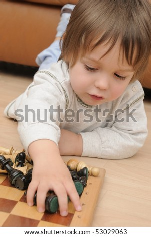 little boy playing with chess figures while laying on the floor