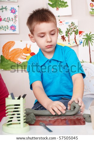 Little boy playing with clay. - stock photo
