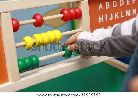 little boy playing with color abacus, education toy,