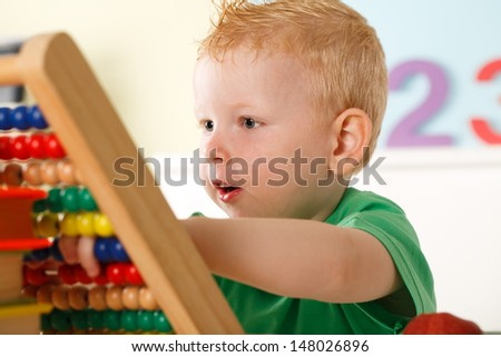 Little Boy Playing with Colorful Abacus Beads - stock photo