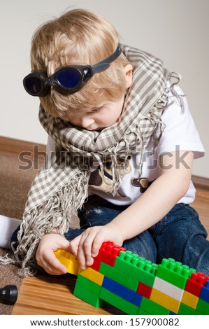 Little boy playing with constructor on floor at home with goggles on his head and scarf around neck - stock photo