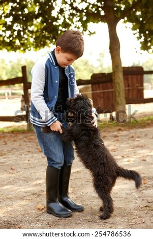 Little boy playing with dog outdoors. - stock photo