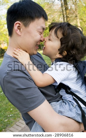 Little boy playing with father, outdoors.
